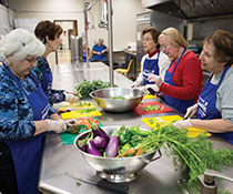 Photo of women preparing food in a kitchen. Links to Gifts of Cash, Checks, and Credit Cards