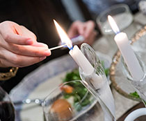 Photo of a person lighting a candle. Links to Gifts That Pay You Income