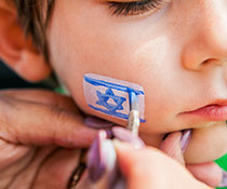 Photo of a boy getting the jewish flag painted on his cheek. Links to Gifts That Protect Your Assets